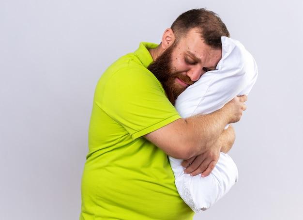 Uomo barbuto malsano sconvolto in polo gialla sentirsi male tenendo il cuscino vuole dormire in piedi sul muro bianco