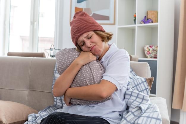 暖かい帽子をかぶった不健康な若い女性を動揺させ、毛布が具合が悪く、風邪やインフルエンザに苦しんでいる病気に見え、明るいリビングルームのソファに座っている顔に悲しい表情を浮かべて枕を持っている