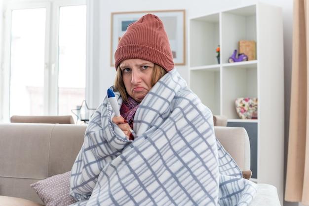 Sconvolto giovane donna malsana in cappello caldo avvolto in una coperta che sembra malata e malata che soffre di raffreddore e influenza con termometro che ha la febbre che sembra preoccupata seduta sul divano in un soggiorno luminoso