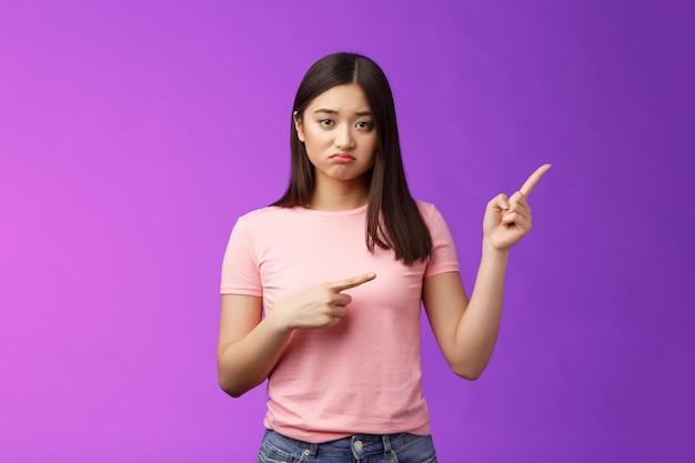 不幸なかわいいやっかいなアジアの女の子が競争に負けて、顔をゆがめた顔をゆがめ、不幸な指差しをしている...