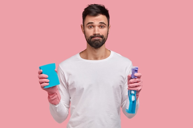Upset unshaven young male janitor holds washing spray and sponge, feels tired after cleaning windows at home, dressed in white casual clothes