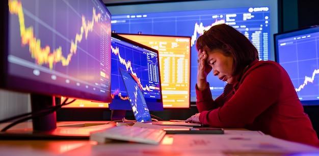 Расстроенный неудачный брокер-трейдер сидит в депрессивном стрессе за рабочим офисным столом в торговой комнате