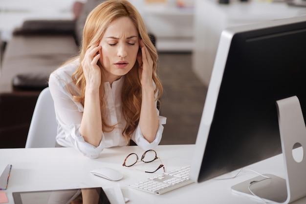 Расстроенный слабый молодой офис-менеджер сидит за столом в офисе и работает, прикасаясь к ее голове и испытывая головную боль