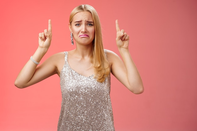 Sconvolto piagnucolando immaturo viziato ragazza bionda ricca in abito scintillante d'argento imbronciato accigliato piangerò indicando rimpianto gelosia implorando comprare scarpe costose, in piedi sfondo rosso dispiaciuto.