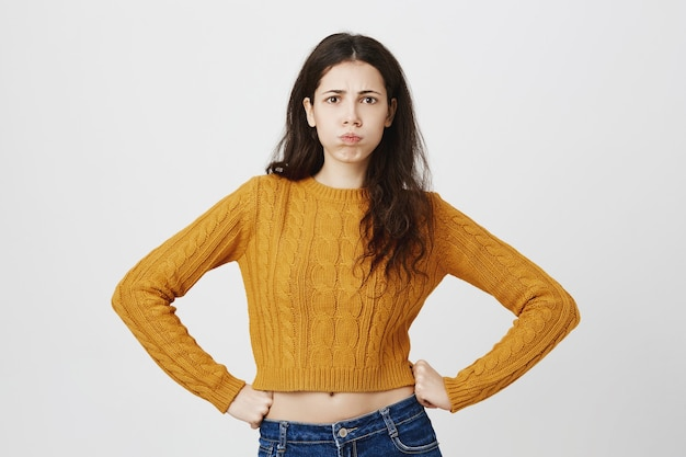 Upset and whining woman pouting, feeling disappointed or angry at someone