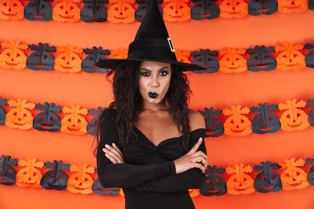 Upset witch girl in black halloween costume standing with arms crossed isolated over orange pumpkin wall