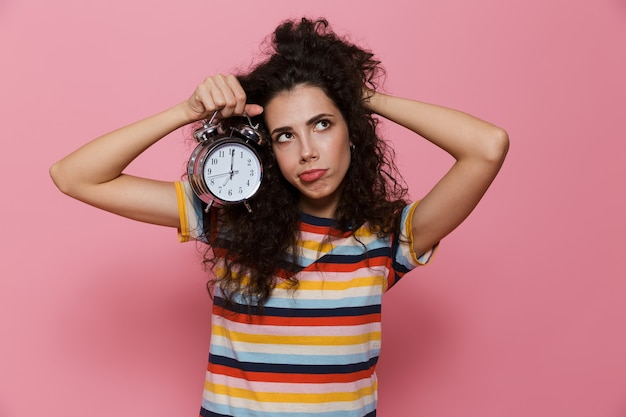 Upset woman 20s with curly hair holding alarm clock isolated on pink