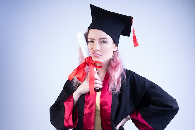 Upset woman in a bachelor cap and mantle holds her graduation certificate