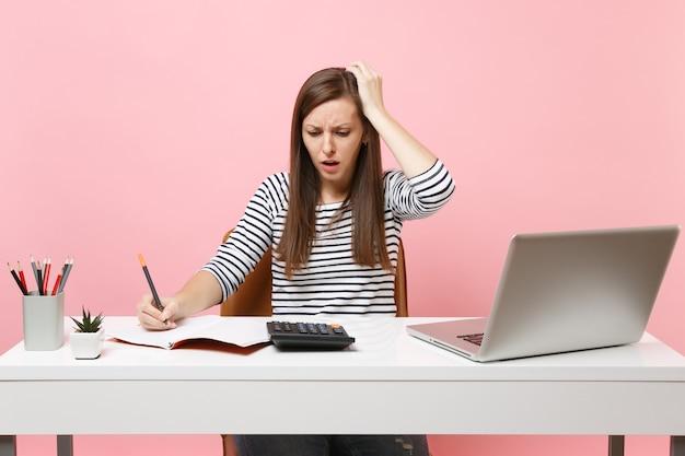 パステルピンクの背景に分離されたpcラップトップでオフィスに座って、計算でメモを書く電卓を使用して頭にしがみついている動揺した女性。業績ビジネスキャリアコンセプト。スペースをコピーします。