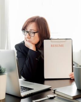 화가 여자는 노트북으로 그녀의 직장 근처에서 손의 얼굴을 닫고 응용 프로그램을 다시 시작합니다.