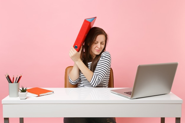 Upset woman defending hiding behind red folder with paper document work on project while sit at office with laptop isolated on pastel pink background. achievement business career concept. copy space.