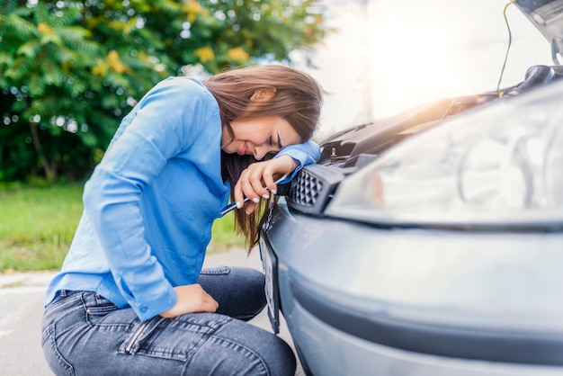 Upset woman emotionally reacting on overheated car. the car standing on the sidelines.