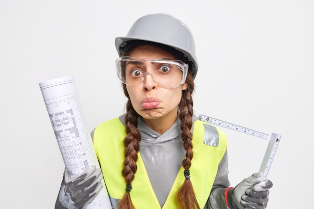 Upset woman engineer makes grimace uses tape measure at construction site holds paper blueprint involved in apartment repai looks sadly at camera