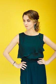 Upset woman in green dress on yellow background. positive emotions