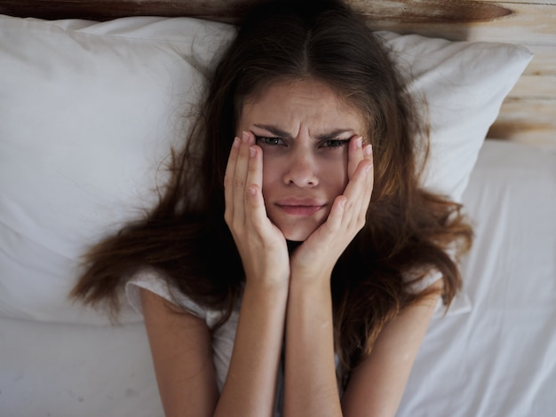 Upset woman holding face with hands while lying in bed health problems