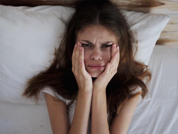 침대 건강 문제에 누워있는 동안 손으로 얼굴을 잡고 화가 여자