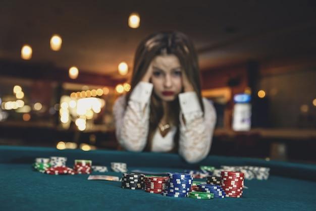 포커 테이블 뒤에 앉아 카지노에서 화가 여자