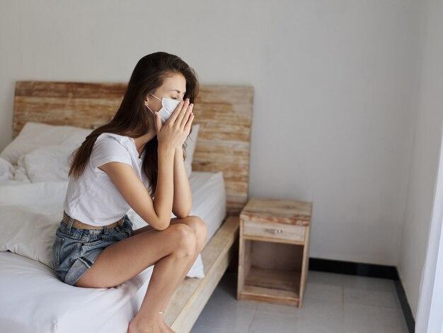 Расстроенная женщина в медицинской маске находится на карантине во время отпуска, изоляция модели стресса