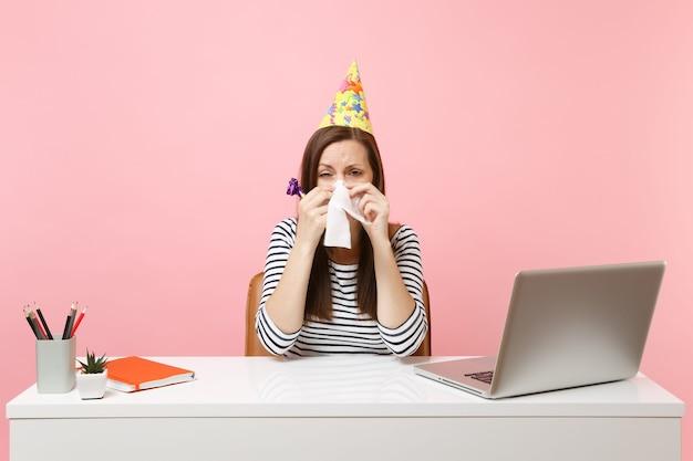 誰もpcのラップトップで白い机で祝うために来なかったのでティッシュで涙を拭くパイプを演奏してパーティーハットで動揺した女性