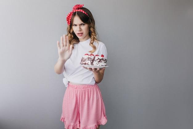 バースデーケーキでポーズをとるピンクのスカートの動揺した女性。分離されたパイを持つスタイリッシュな女の子。