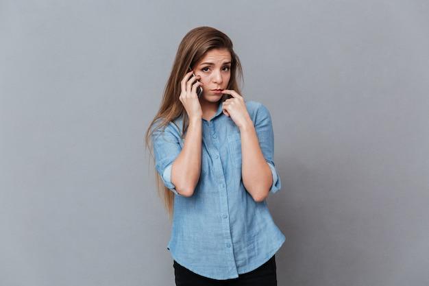 電話で話しているシャツの動揺の女性