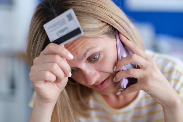 ストレスで動揺している女性は銀行カードを保持し、電話電話詐欺の概念で話します
