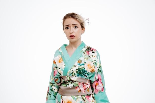 흰색에 슬픈 표정으로 옆을 바라보는 전통적인 일본 기모노를 입은 화난 여자