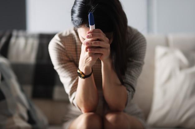 화난 여성이 소파에 앉아 계획에 없던 임신 테스트기를 들고 있다