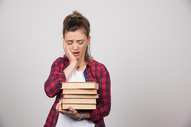 Una donna sconvolta che guarda una pila di libri su un muro grigio.
