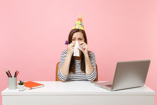 Upset woman in party hat with playing pipe wiping tears with tissue because nobody came to celebrate at white desk with pc laptop isolated on pink background. achievement business career. copy space.