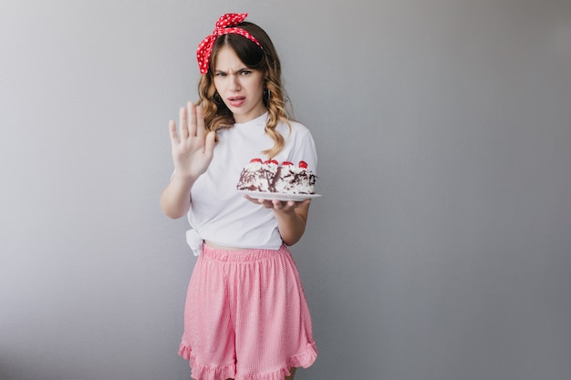 Upset woman in pink skirt posing with birthday cake. stylish girl with pie isolated.