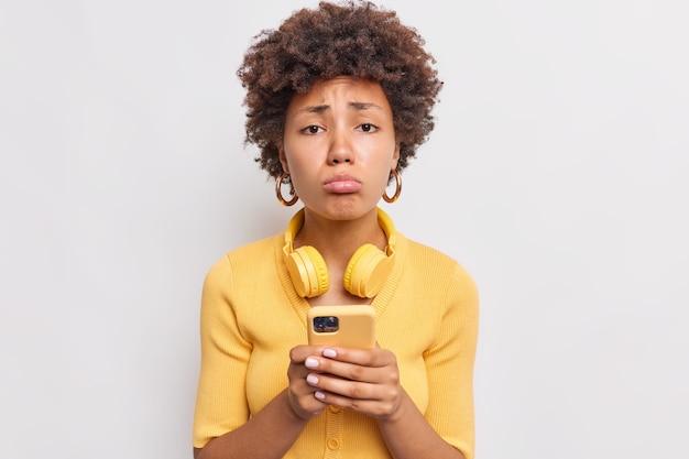 Расстроенная женщина сжимает губы, грустно смотрит спереди, получает неприятное сообщение или уведомление на мобильный телефон, одетая небрежно, использует стереонаушники, изолированные на белой стене