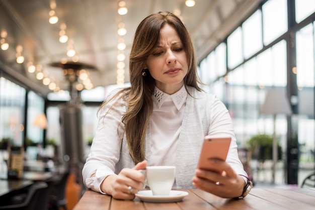 Upset woman reading message on phone in cafe.