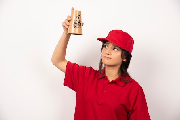 Donna turbata in uniforme rossa che tiene una tazza vuota