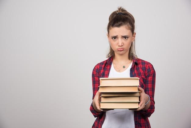 Una donna sconvolta che mostra una pila di libri su un muro grigio