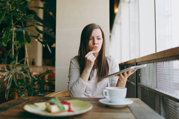Upset woman sitting alone near big window in coffee shop with cup of cappuccino, cake, relaxing during free time. female working, reading bad news on pc tablet computer rest in cafe. lifestyle concept
