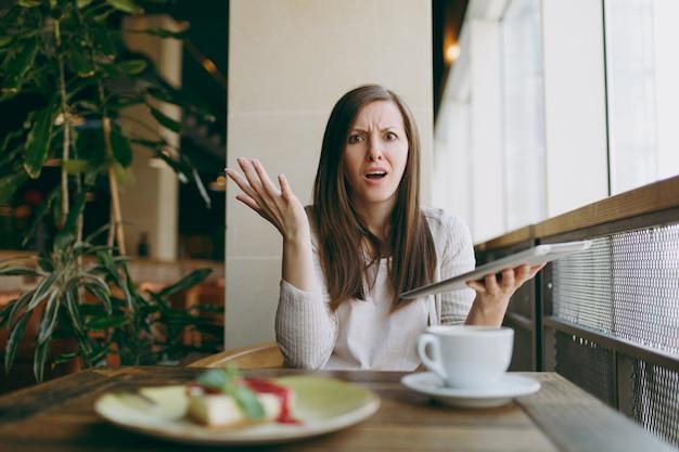 カプチーノ、ケーキ、自由な時間の間にリラックスしてコーヒーショップの大きな窓の近くに一人で座っている動揺した女性。女性が働いて、pcタブレットコンピューターで悪いニュースを読んで、カフェで休んでいます。ライフスタイルのコンセプト