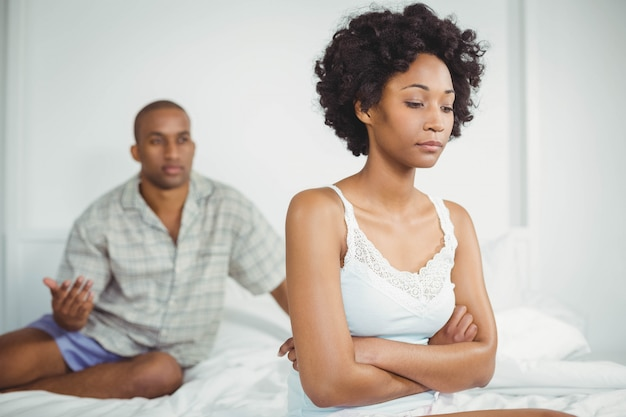 Upset woman sitting on bed after arguing with her boyfriend