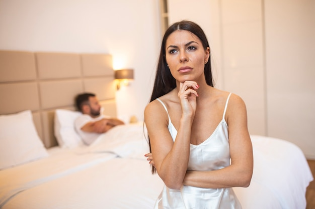 Upset woman sitting on the bed with man in the background.