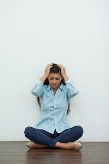 Upset woman sitting on floor and clutching head