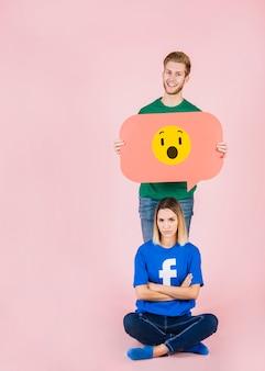 Upset woman sitting in front of happy man holding shocked emoji speech bubble