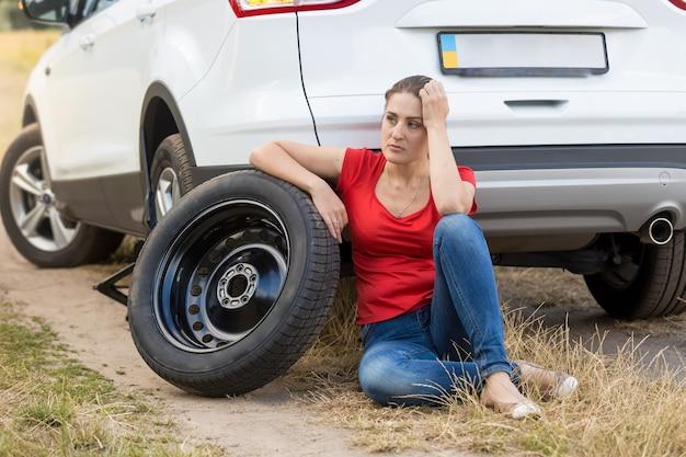 깨진 차에 바닥에 앉아 화가 여자