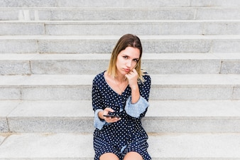 Upset woman sitting on staircase holding cellphone
