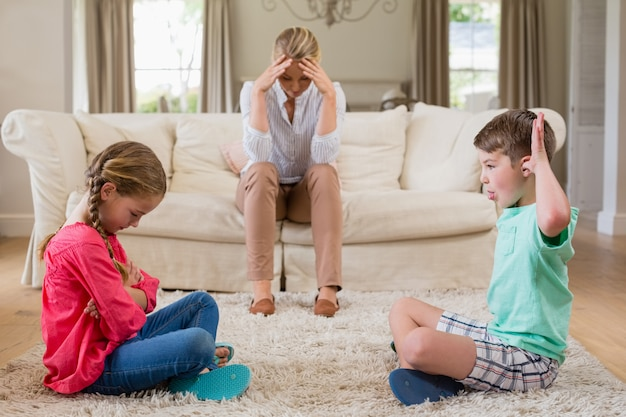 Upset woman sitting on sofa while brother teasing sister