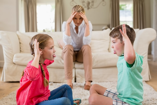 Upset woman sitting on sofa while siblings teasing each other
