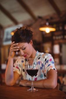 額に手で座っている動揺の女性