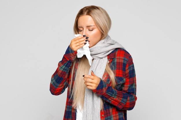 Upset woman sneezing and blowing nose with tissue