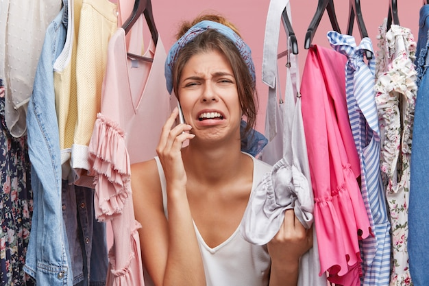 Upset woman standing near rack of clothes, chatting over smart phone with her friend, complaining that she has nothing to wear. displeased female not knowing what to put on for birthday party