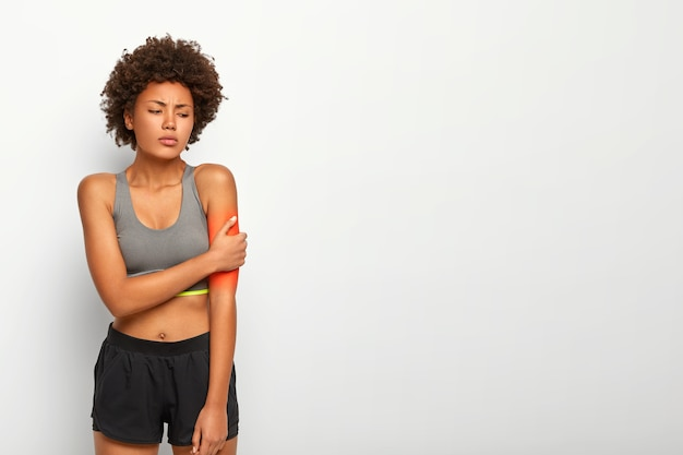 Upset woman touches arm, suffers from painful feelings, hurted hand during fitness training, dressed in casual top and shorts, poses indoor over white studio wall