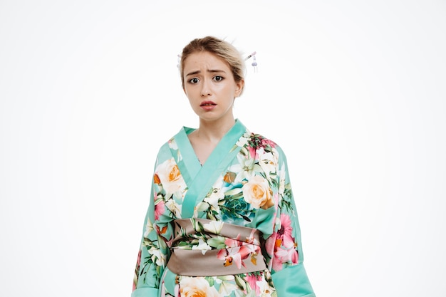 Donna turbata in kimono giapponese tradizionale che guarda da parte con espressione triste su bianco